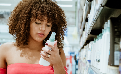 Woman with curly hair reads the ingredients on a bottle while standing in a store aisle