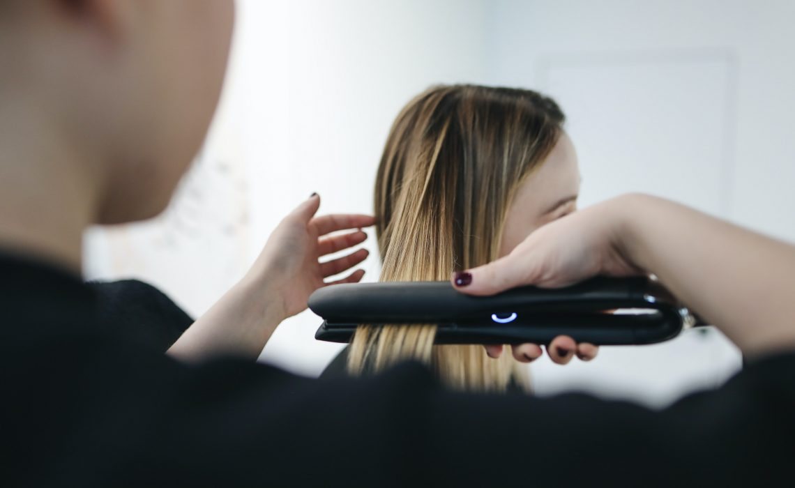 photo of woman's hair being straigtened