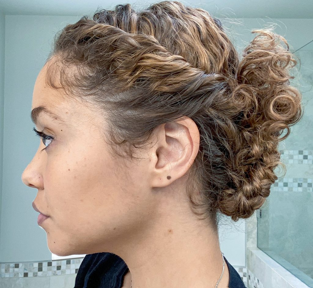 Updo with hair rolled down side into two braided buns at the base