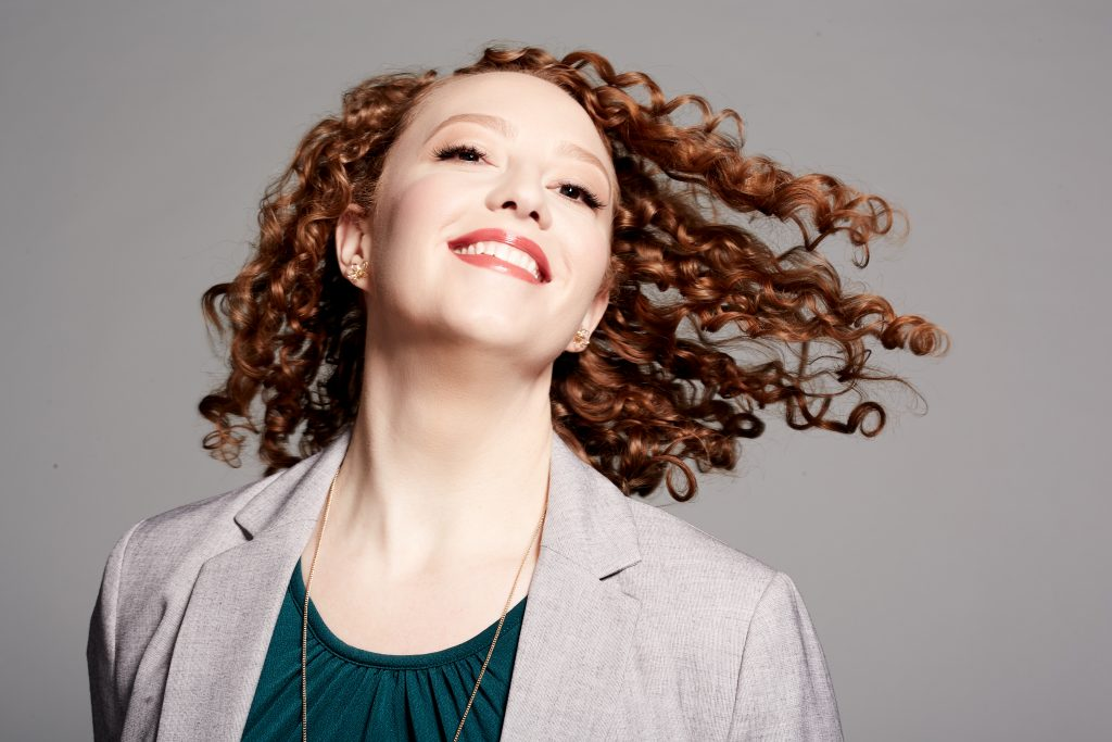 Stephanie smiles and tosses her red curly hair