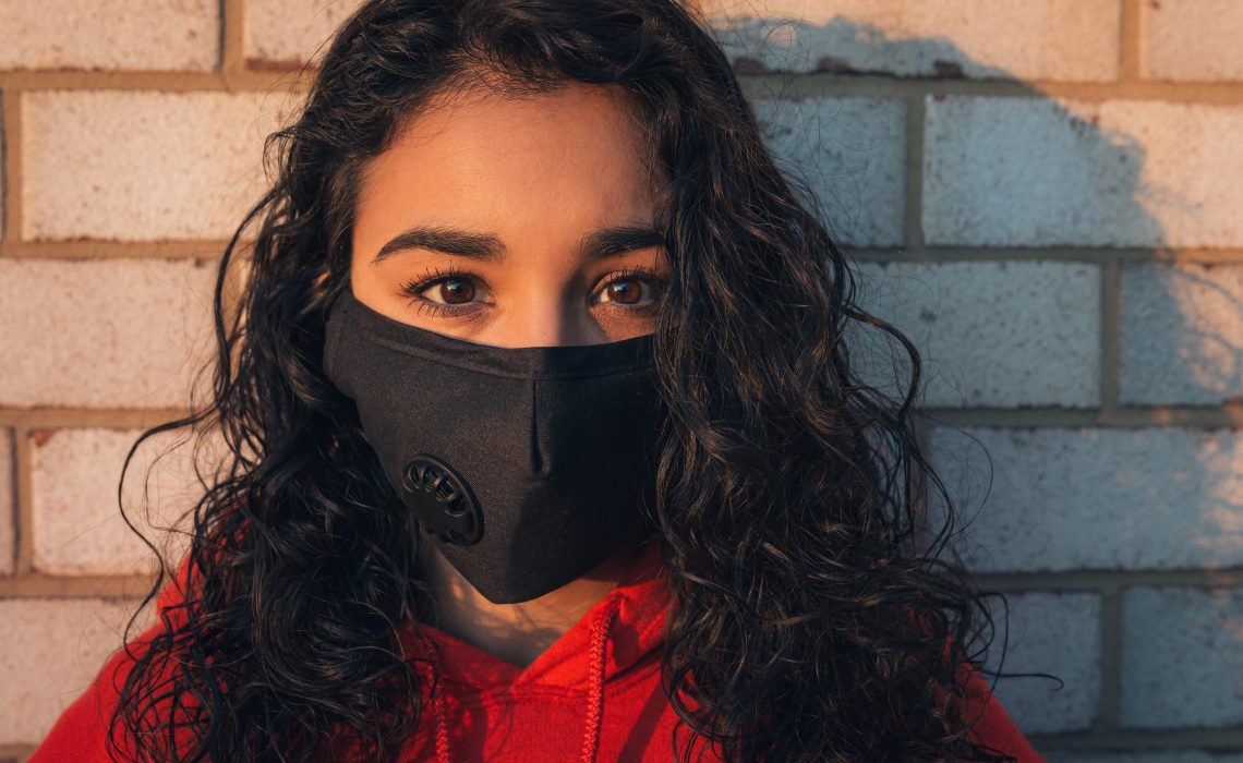 photo of a curly haired woman wearing a mask