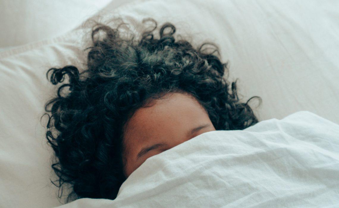 photo of girl under blankets